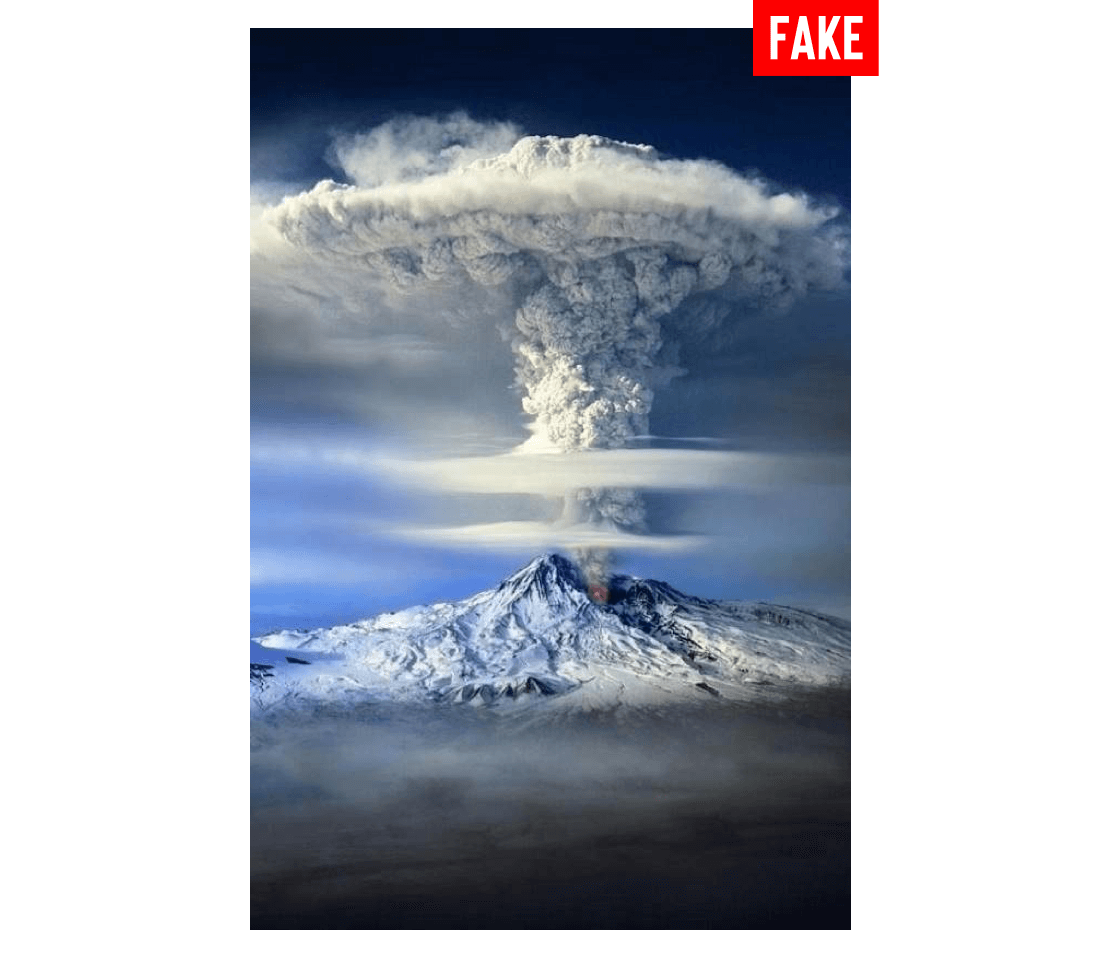 Photo labeled fake of a snowy mountain with a mushroom cloud eruption coming from the peak.